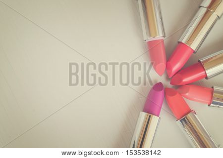 Collection of lipsticks with copy space on beige background, retro toned