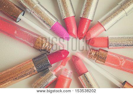 pile of wet coloful lipsticks close up, retro toned