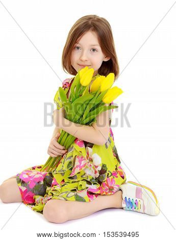 Adorable little Caucasian girl in summer dress holding a bouquet of yellow tulips.Isolated on white background.