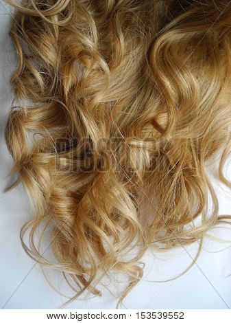 Blonde long women's curly hair close up.
