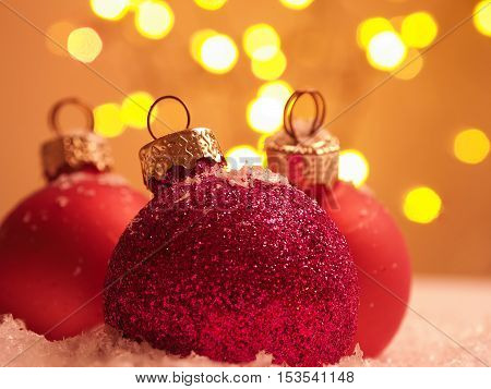 Three Christmas baubles in snow with a beautiful bokeh background