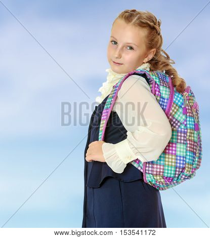 Dressy girl schoolgirl in black dress and white shirt with a knapsack on her shoulders. Close-up.On the pale blue background.