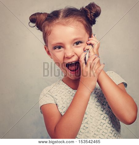 Excited Kid Girl Talking On Mobile Phone With Opened Mouth On Blue Background. Vintage Toned Closeup