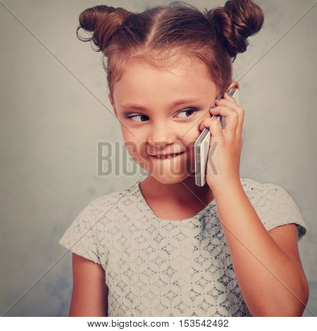 Funny Kid Girl Talking On Mobile Phone With Happy Smile On Blue Background With Empty Copy Space. To