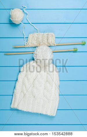Knitted white scarf and hat on the blue wooden background.