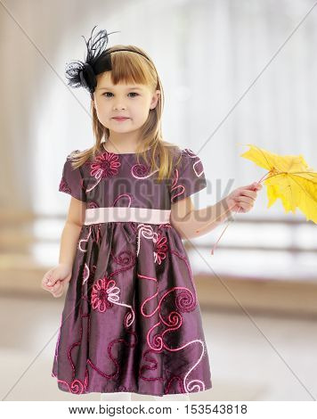 In a room with a large semi-circular window. Adorable little girl holding a maple leaf.