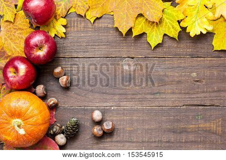 autumn thanksgiving background with seasonal fruits and vegetables colorful leaves and nuts. happy thanksgiving greeting card