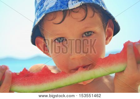 Boy in a hat sitting juicy watermelon. Exotic fruit on vacation.