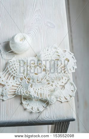 Closeup of handmade crocheted white napkins on white table