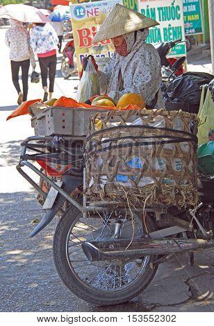 Vinh, Vietnam - May 29, 2015: woman is uploading vegetables on her bicycle outdoor in Vinh, Vietnam