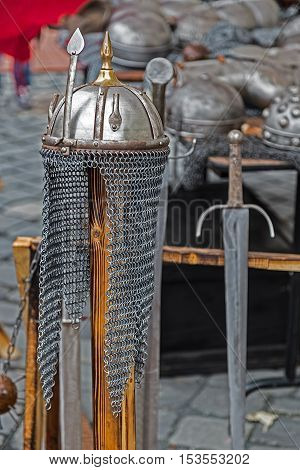 Armor and medieval weapons on display at a street exhibition.