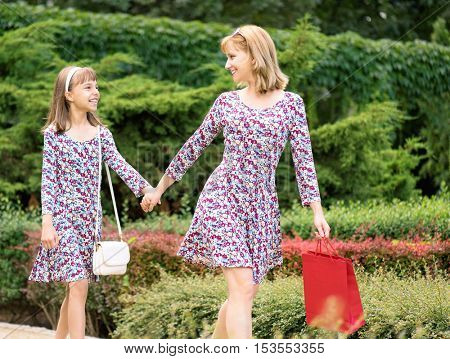 Attractive smiling mother and daughter having fun together during shopping trip. Beautiful happy family walking with colorful shopping bag and holding hands. The same dress.