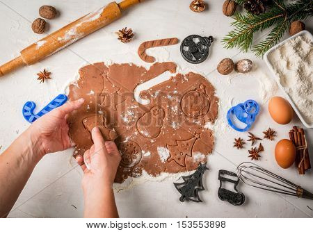 Girl cooking traditional christmas gingerbread cookies, cutting its with cuttings for dough. Christmas-tree branches, a rolling pin, whisk for whipping eggs, nuts and cones they lie on a table nearby