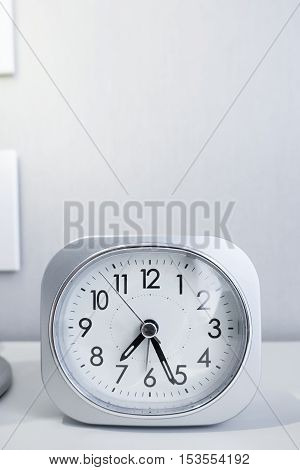 White Square Clock On White Bed Stand With White Wallpaper Background, Morning Time In Minimal Style