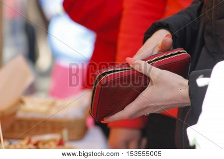Woman with long nails holding a red wallet at street market.