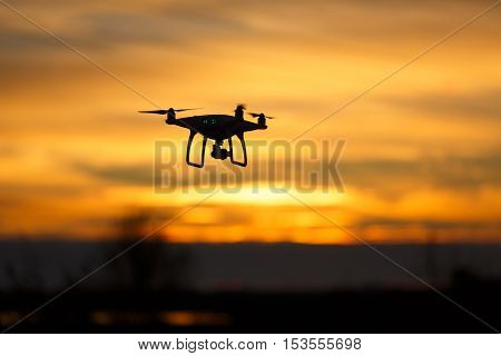 Flying quadcopter drone is recording a sunset