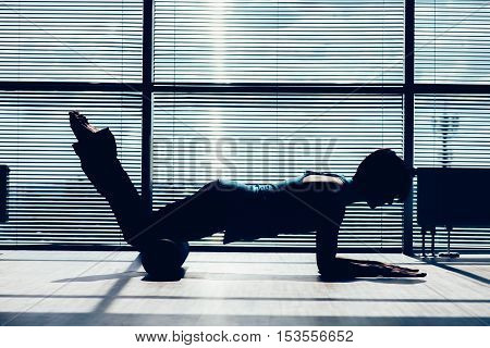 fitness, sport, training and lifestyle concept - woman doing pilates on the floor with foam roller. contour of the body against the window