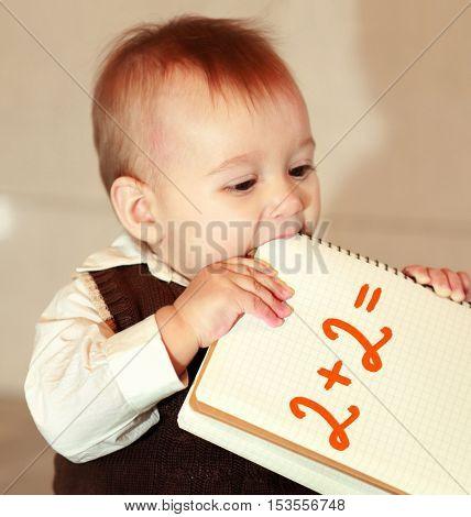 little boy studies a notebook, learns surrounding objects