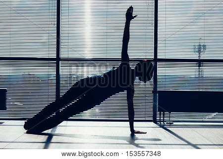 fitness, sport, training and people concept - smiling woman doing abdominal exercises on mat in gym. contour of the body against the window
