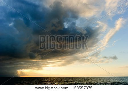 Sunset ocean storm clouds is a poerful cloudscape with sun rays bursting over the open sea.