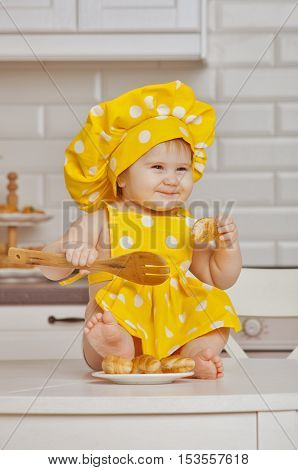 child in a yellow suit of the cook in white peas on a kitchen tableholds in hand croissant and a wooden shovel on a table in a plate croissants
