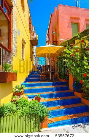 Rethymnon, Island Crete, Greece - July 1 2016: Cozy small Cretan cafe and colorful stairs between nice cretan houses