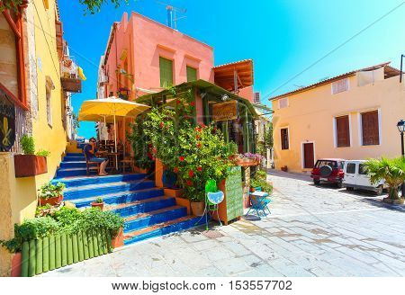 Rethymnon, Island Crete, Greece - July 1 2016: Cozy Cretan small cafe with flowers outside with ad on the green board about Cretan cuisine