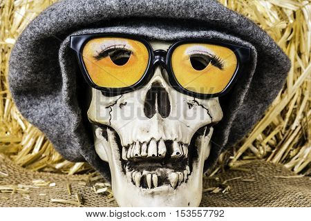 Halloween skull with 3D glasses and wool cap on burlap in front of bale of straw