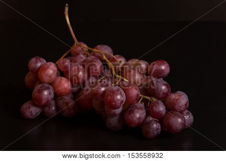 A bunch of red grapes over a black background
