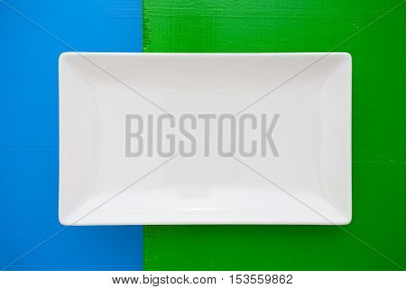 Empty white ceramic dish on over blue and green wooden tablerectangle dish