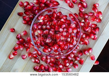 Pomegranate seeds in glass bowl on bamboo choping board