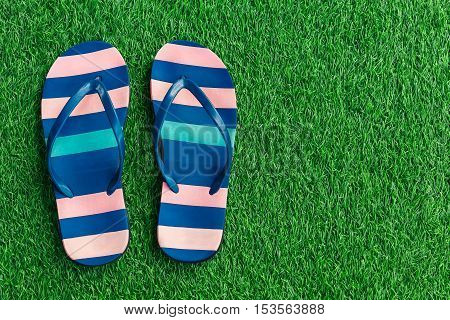 Closeup of bright flip flops on green grass. A bright Sunny day. The rest of the sea.