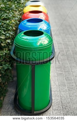 Colored trash containers for garbage separation. Taking care of nature and ecology. The greenery around. Containers for plastic, paper, glass and metal.