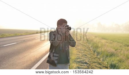 Landscape professional photographer taking a picture near a road with the sunrise in the background