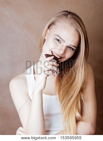 young beauty blond teenage girl eating chocolate smiling, lifestyle people concept close up
