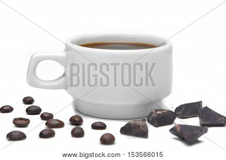 white cup of espresso on a white background decorated with coffee beans and chocolate