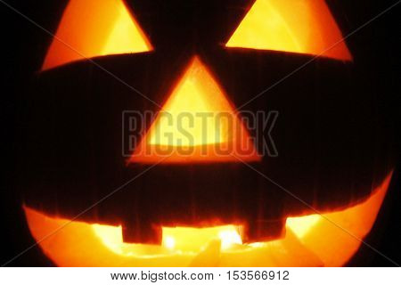 close up of halloween pumpkin with lit candles