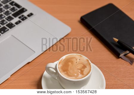 The cup of coffee on the flat workspace with paper notebook pen and notebook's keyboard on the background. Relax during business day concept.