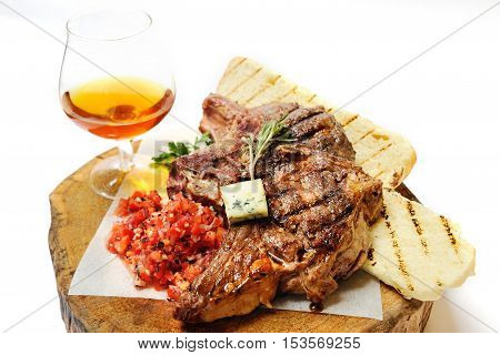 fried steak on a wooden board, a glass of brandy and bread with spices