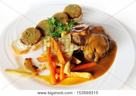 Ossobuco with falafel pumpkin on a white background
