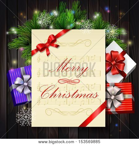 Christmas card with notes and music with holy and gift boxes on wooden background