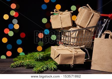 Shopping trolley with gift boxes and brenches of fir-tree with decoration on a black background with light of garland. Christmas and New Year sale.