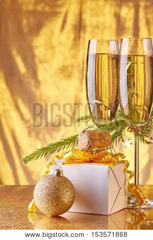 Two glasses with champange, fir tree branch, gift box and christmas toy on a gold background. New year and Christmas.