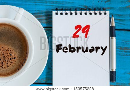 February 29th. Day 29 of month, calendar in notepad on wooden background near morning cup with coffee. Winter time. Empty space for text.