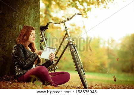 Outdoor nature fitness internet technology concept. Girl under tree with bike. Young redhead lady resting after cycling browsing websites on tablet.