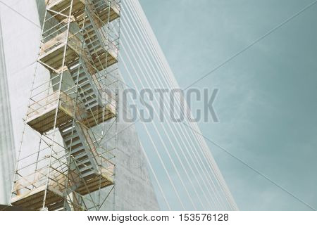 Rope bridge under construction with regular metal ropes and scaffolding on a sunny summer day in Rio de Janeiro with clear sky above view from bottom