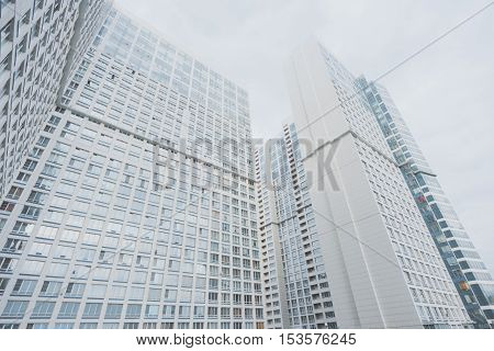 White contemporary residential skyscraper apartment building in Moscow on a cloudy day with regular windows view from bottom