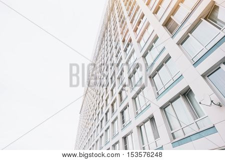 Facade of contemporary residential skyscraper apartment building in Moscow on a cloudy day with a lot of regular windows view from bottom