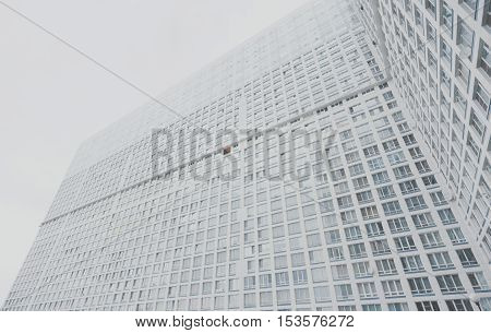 Huge contemporary white and grey residential skyscraper apartment building with multiple regular windows on facade Moscow bright cloudy day view from bottom