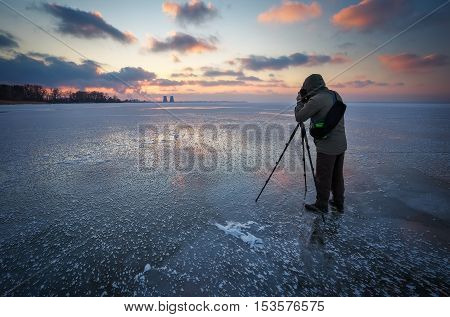 Photographer takes a picture of sunset on a frozen river in winter